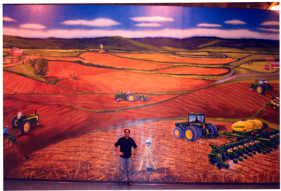 Mural of a man standing in the middle of a field during harvest time